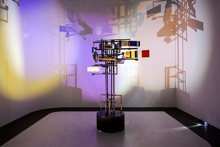 A sculpture made of metal rods and coloured panels stands on a black podium, its shadow cast on the walls in different colours.