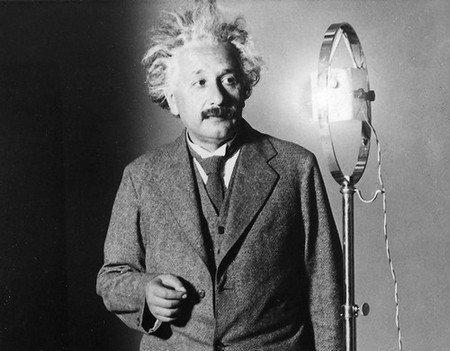 Black and white photo of Albert Einstein, a white man with wild hair and a moustache, standing next to a 1920s microphone.