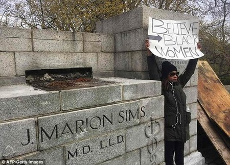 Only three of Sims' dozen slaves are named, Betsey, Lucy and Anarcha; he operated on them without anesthesia while his white patients were medicated. Pictured: an activist at the removal on Tuesday