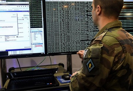 A military cyberdefence specialist stares at a computer screen
