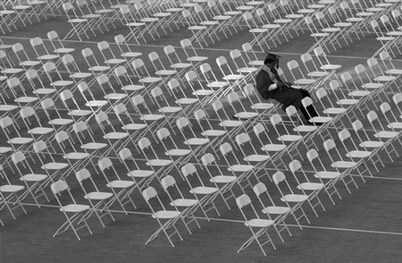 Graduate sits alone in rows of white chairs