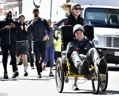 Kaitlyn Kiely, 30, is pictured pushing her boyfriend Matt Wetherbee, 30, along the Boston Marathon route on Monday as friends cheer them on in the background