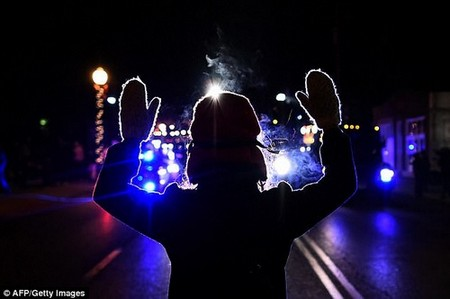 A protester holds her hands up in front of a police car in Ferguson, Missouri, in 2014 after the fatal shooting of a 18-year-old black teenager Michael Brown. It was one of many protests in the Black Lives Matter movement as agencies started to count how many more youths of color were being shot than white people