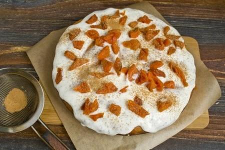 Покрываем тыквенный пирог кремом, посыпаем сухофруктами и корицей