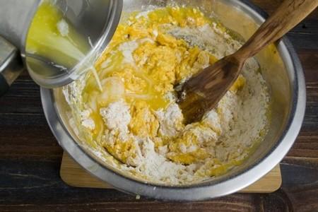 Добавляем измельчённую в блендере тыкву и растопленное сливочное масло. Замешиваем тесто