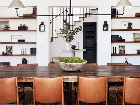 To accommodate the scale of the dining room, Arnold commissioned a custom table made from reclaimed white oak by designer Cooper Reynolds. An industrial lighting fixture from Urban Electric mimics its linear footprint; the midcentury chairs were sourced from Lief.