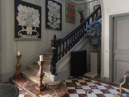 Along the central stairwell, two black-and-white paintings are by the homeowner's friend, the French artist Jean Clerté. The next painting is by French artist Claude Viallet. The deer is in papier-mâché with wooden branches for horns. The floor is original to the building.
