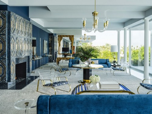 Dark-blue hues dominate the ample glass-walled living room. The palette was inspired by the space's original fireplace, whose strikingly elaborate tiles once covered the ceiling of an Italian chapel (or so the story goes). While most of the furnishings seen here are designs by Charles Hollis Jones, the central lacquered table with brass details is a 1970s piece by Jean-Claude Mahey.
