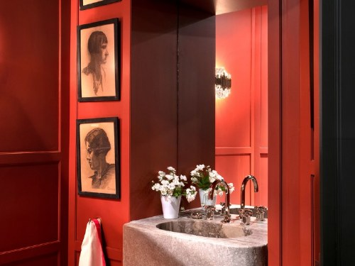 A powder room is painted in a red by Atelier Mériguet-CarrÈre. Silver travertine sink by Charles Zana.
