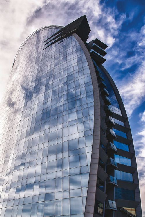 The sleek, mirrored side of the W Barcelona reflects the sky over the Spanish city.