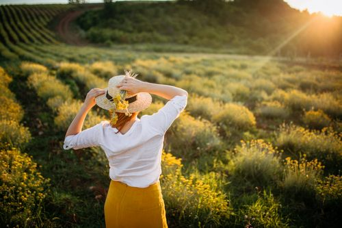 Boho style woman with hat enjoying the sunset in everlasting flowers field