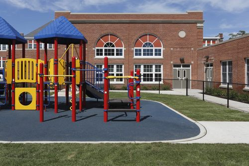 gated elementary school playground with colorful jungle gym equipment, slides, monkey bars, mazes, on padded play surface, with large brick school building complex